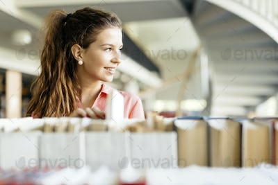 Woman choosing a book from the shelf in a library