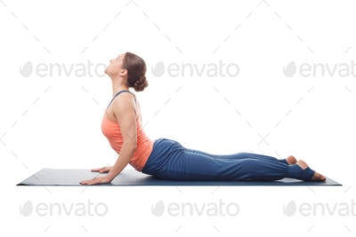 Sporty fit yogini woman practices yoga asana bhujangasana