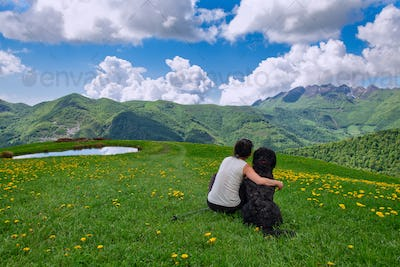 A girl with her big dog looks at the landscape in the mountains