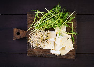 Soft brie cheese and microgreens on a wooden board