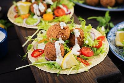 Tortilla wrap with falafel and fresh salad. Vegan tacos. Vegetarian healthy food.