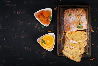 Orange cake with dried apricots and powdered sugar. Top view