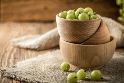 Fresh gooseberry in a wooden bowl.