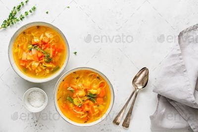 Spring vegetable soup with chicken stock for two person on white table. Top view, copy space.