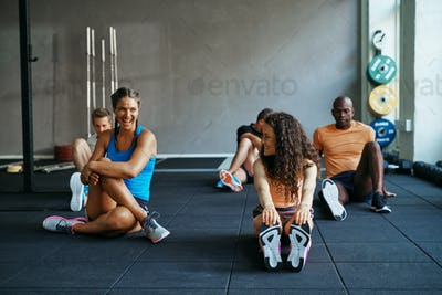 People talking together on a gym floor after working out