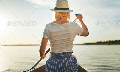 Young woman canoeing on a scenic lake in the summer