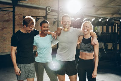 Smiling group of friends standing together after a gym workout