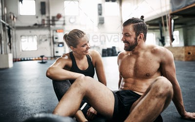 Fit couple smiling and talking during a break from exercising