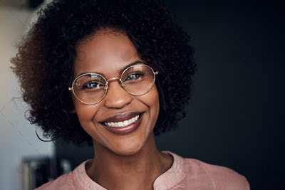 Smiling young African businesswoman standing in an office