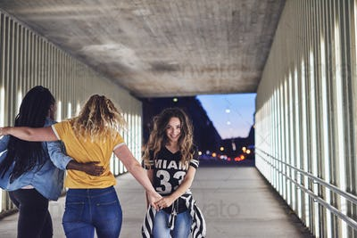 Laughing young women walking together through the city at night