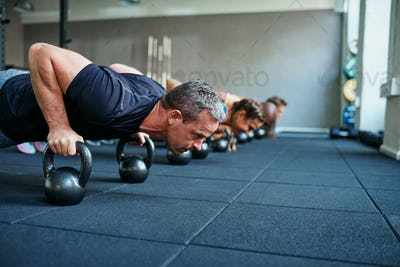 Fit people doing pushups on weights in a gym class