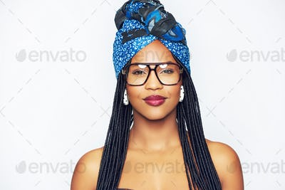 Black woman in ethnic head wrap looking at camera