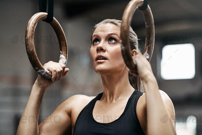 Fit woman preparing to workout on rings at the gym