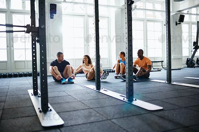 Smiling group of people doing crunches together in a gym