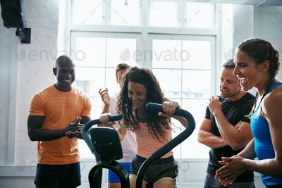 People cheering on their friend riding a health club bike