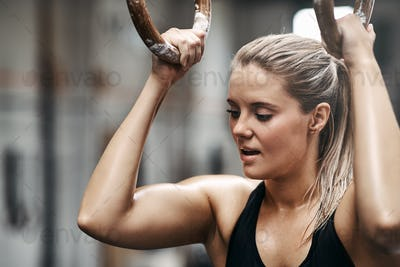 Woman working out on rings during a gym exercise session