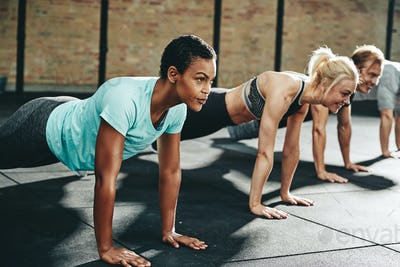 Fit young people doing pushups together on a gym floor