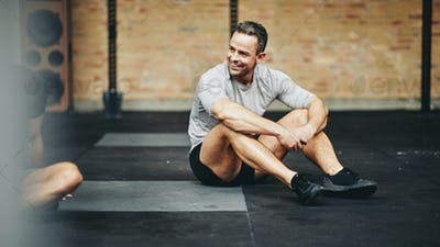 Smiling man sitting on a gym floor after working out