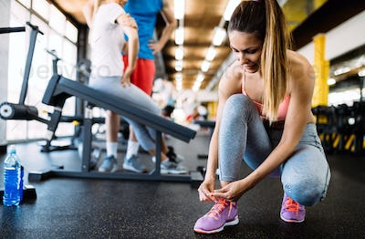Attractive sportswoman tying shoelaces at gym
