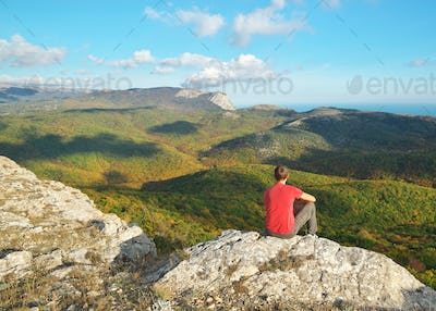 Man sitting on the edge of cliff mountain.