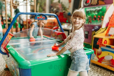 Two happy girls plays air hockey in game center