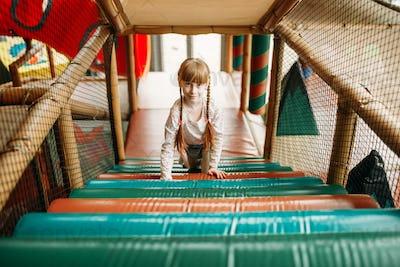 Funny girl in climbing zone, children game center