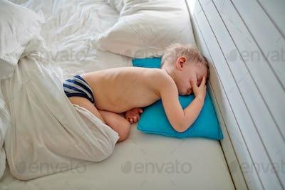 Toddler boy sleeping on blue pillow