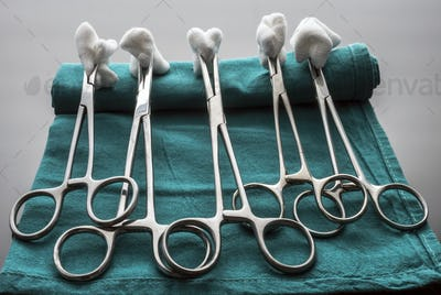 Scissors surgical with torundas in an operating theater, composition horizontal, conceptual image
