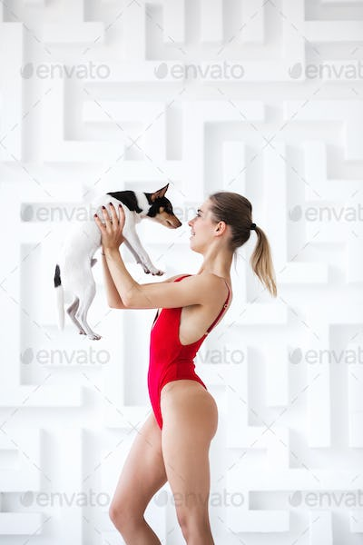 Beautiful woman posing in red bodysuit with a dog in the studio.