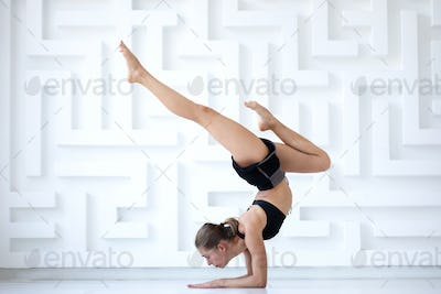 Fitness woman doing handstand in sport studio.