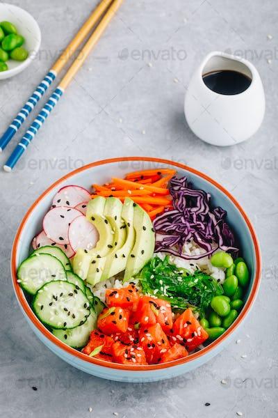 Salmon poke bowl with rice, avocado, seaweed, carrots, cucumber, radishes and edamame beans