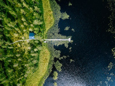 Aerial view of blue lake with green forests in Finland.