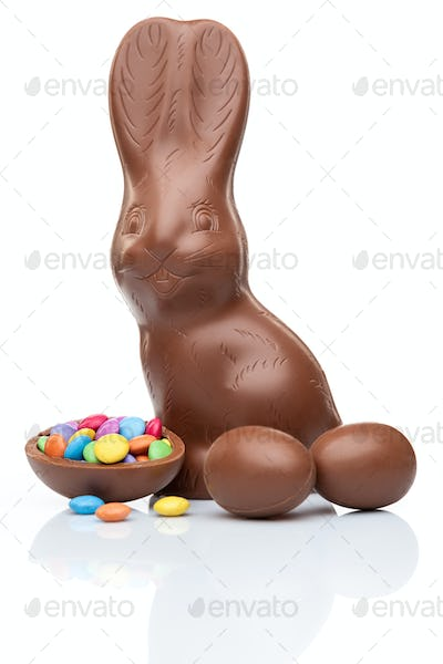 Chocolate Easter bunny, eggs and sweets on white background