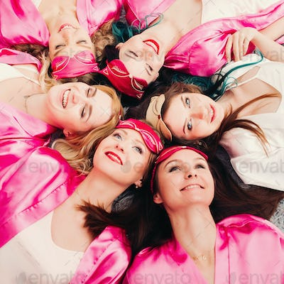 Portrait of beautiful girls in pink robes celebrating bridal shower
