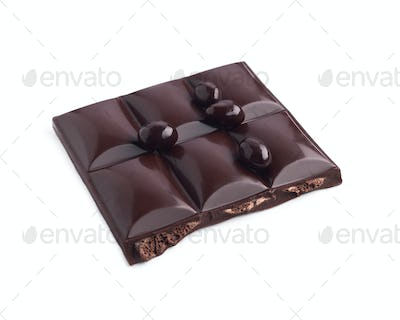 piece of shiny black chocolate and chocolate balls, isolated on white background