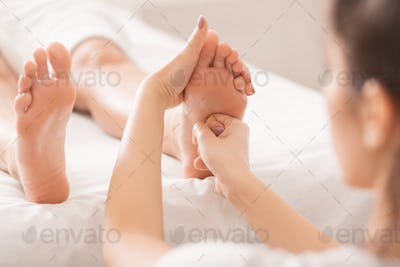 Foot massage. Woman relaxing at spa salon