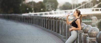 Sporty millennial woman drinking water after run practice on bridge