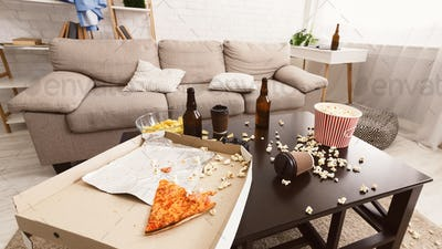 After party interior chaos. Beer bottles, popcorn and pizza