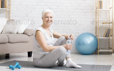 Senior woman resting on exercise mat after fitness workout