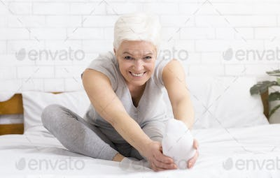Charming cheerful mature woman stretching her legs