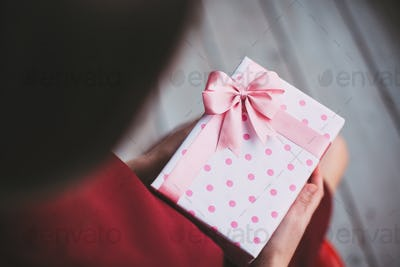 Gift with pink ribbon in female hands.