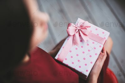 Gift with pink ribbon in female hands. Top view.