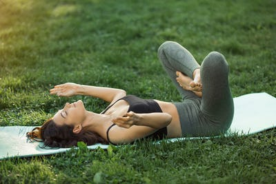 Funny photo about young woman doing yoga exercise and fooling around outdoors in park at morning