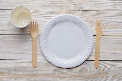 Wooden single use kitchenware on white table. Top view, space fo