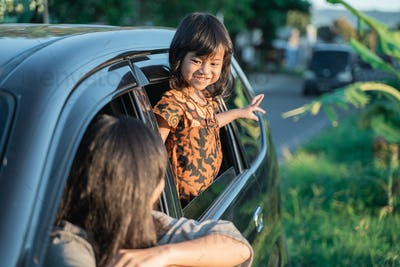 mother with daughter enjoy sunset from inside car