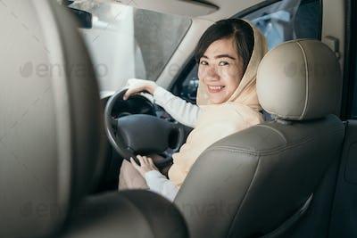 muslim woman with hijab driving a car