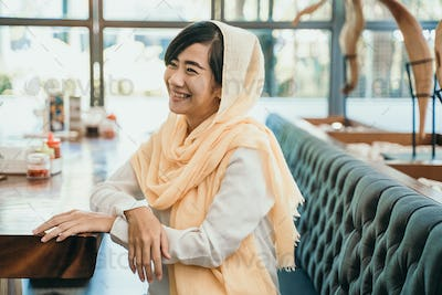 smiling muslim girl in cafe