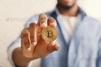 Golden bitcoin in african-american man hand closeup