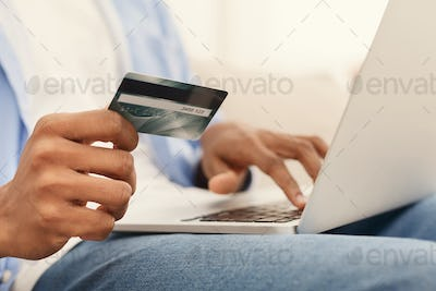 Man purchasing product online, using credit card to pay