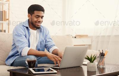 Millennial black man working on laptop in home office